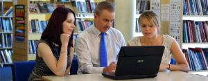 three teachers at a lap top discussing CPD