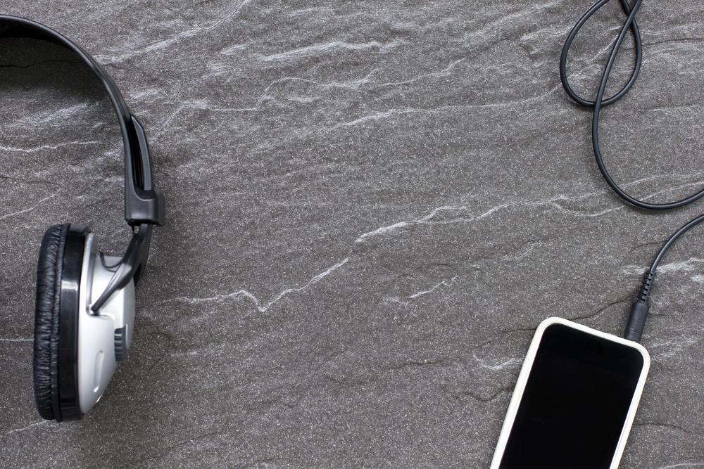 Music headphones on a detailed stone surface with a music player attached