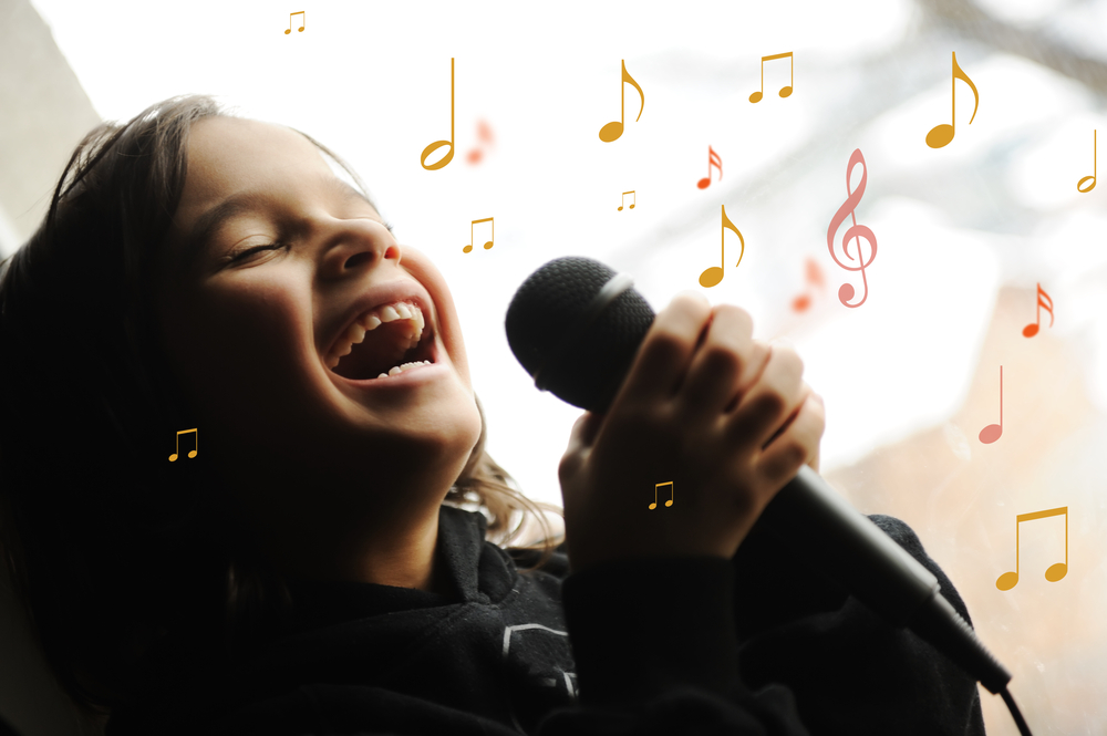 Musician kid singing a song with microphone