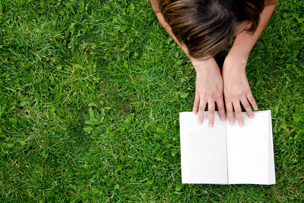 Person lying outdoors and reading a book