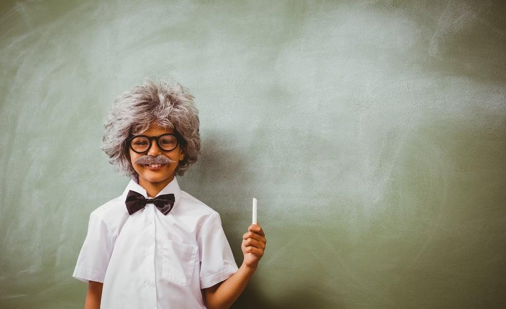 Portrait of little boy dressed as senior teacher in front of blackboard.jpeg