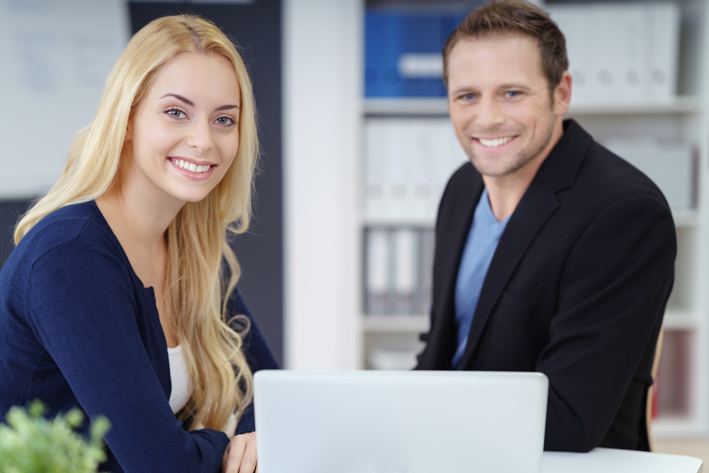 Successful young business couple working together on a self-employed business posing at a desk in their office smiling at the camera