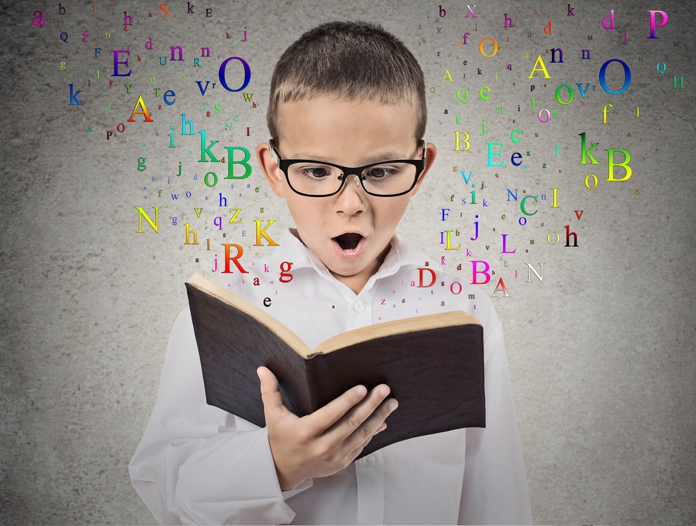 Surprised child reading a book with letters flying away from it isolated on grey wall background. Face expression. Education concept