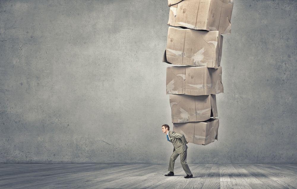 Young businessman in suit carrying big stack of carton boxes