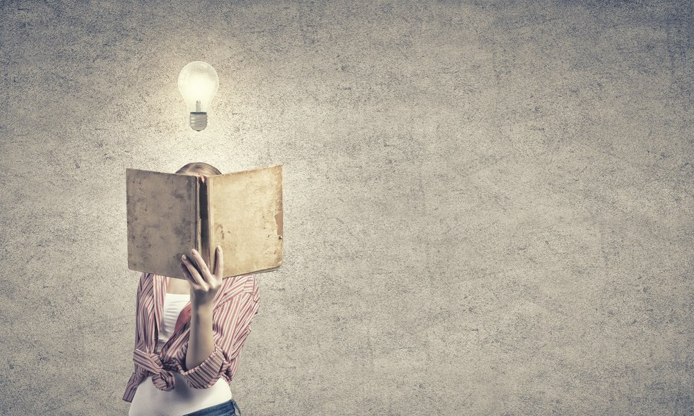 Young funny girl with opened book in hands