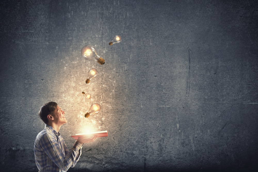 Young man holding opened book with glass glowing light bulbs flying out-1
