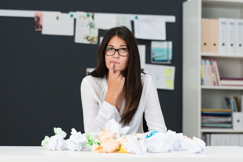 Young woman with writers block sitting in an office with a desk littered with crumpled paper as she sits looking thoughtfully into the air with her finger to her chin seeking new ideas-1